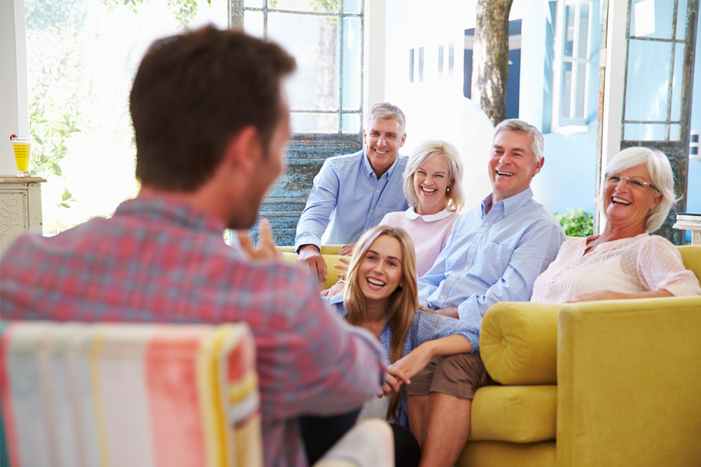 Image of family laughing together, sitting down on sofa and chair